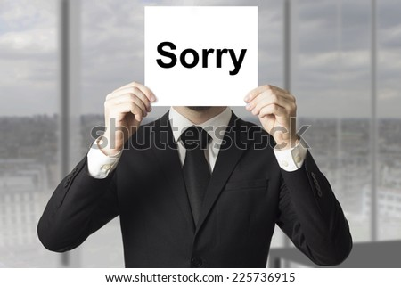 businessman in black suit hiding face behind sign sorry - stock photo