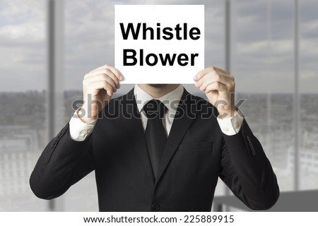 businessman in black suit hiding face behind sign whistle blower - stock photo