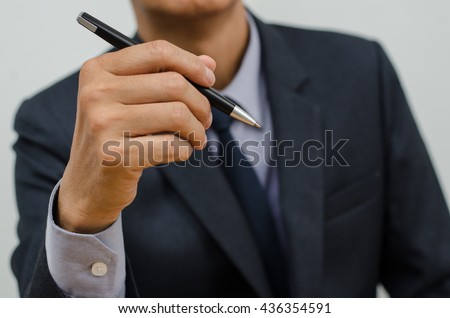 Businessman in black suit holding black ball point pen during working, close up.