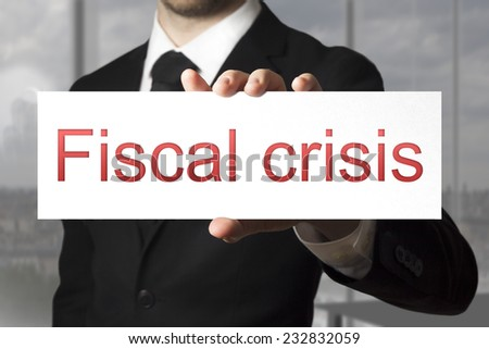 businessman in black suit holding sign fiscal crisis - stock photo