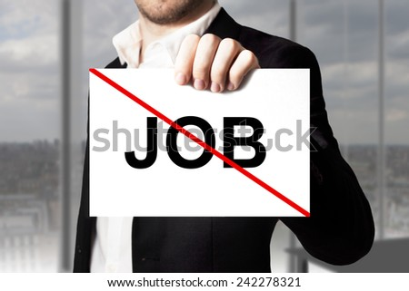 businessman in black suit holding sign job crossed out jobless - stock photo