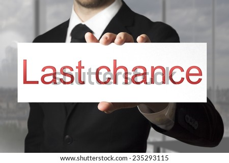 businessman in black suit holding sign last chance - stock photo