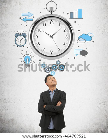 Businessman in black suit is standing in front of concrete wall with stopwatch sketch on it looking up and thinking. Concept of time management