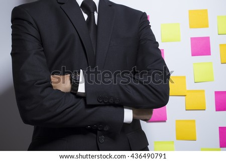 Businessman in black suit on notepaper background