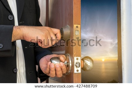 businessman in black suit open the door by key  to seascape can use to display or montage product or concept sea view point - stock photo