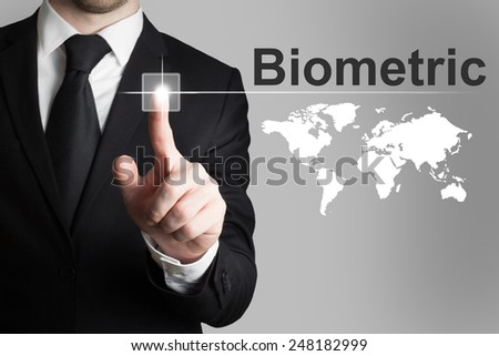businessman in black suit pushing button biometric worldmap - stock photo