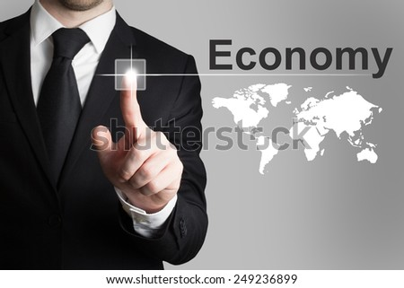 businessman in black suit pushing button economy worldmap - stock photo