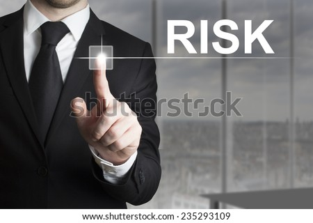 businessman in black suit pushing button risk - stock photo