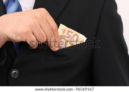 Businessman in black suit putting 50 Euro in the own pocket - stock photo