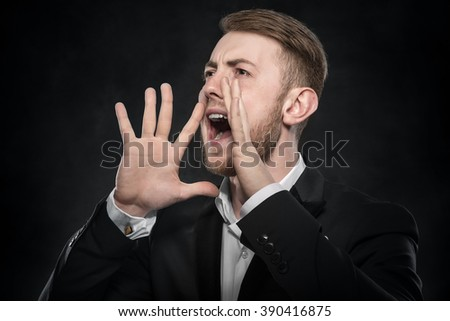 Businessman in black suit shouts lifting his hands up. on a dark background. - stock photo