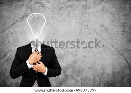 Businessman in black suit with light bulb instead head, on concrete background with copy space