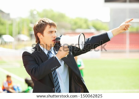 Businessman in black suit with loudspeaker at athletic stadium - stock photo