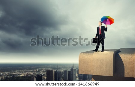 Businessman in black suit with umbrella atop of building - stock photo