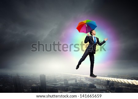 Businessman in black suit with umbrella balancing on rope - stock photo
