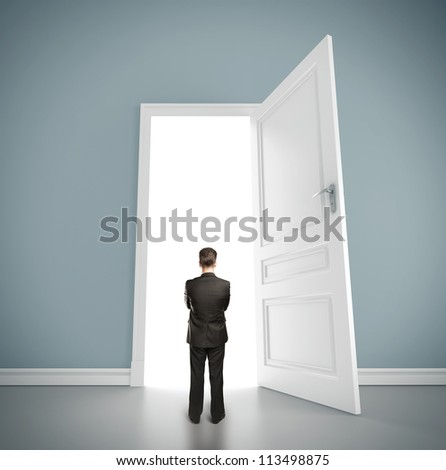 businessman in blue room with doors open - stock photo