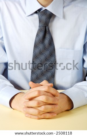 Businessman in blue shirt. Hands clasped. - stock photo