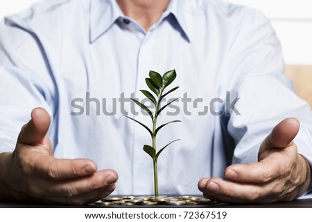 Businessman in blue shirt protecting with hands green plant growing out of coins pile symbolizing safe growth of financial wealth. - stock photo