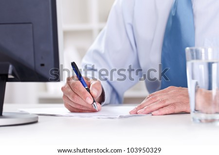 Businessman in blue shirt sitting at office desk signing a contract - stock photo