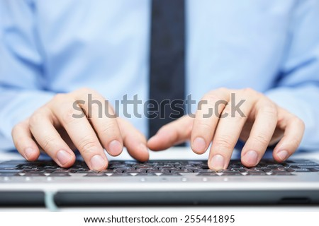 Businessman in blue shirt typing on computer keyboard - stock photo