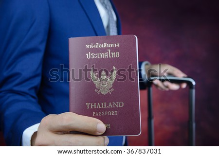 businessman in blue suit showing passport with suitcase - stock photo