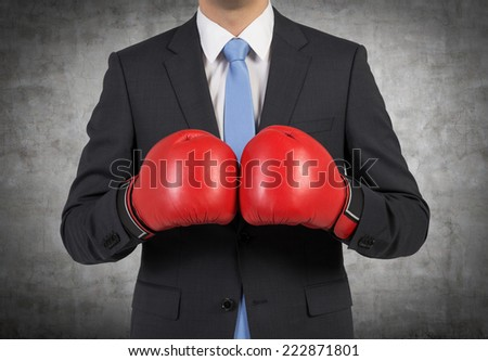 Businessman in boxing gloves, concrete background.