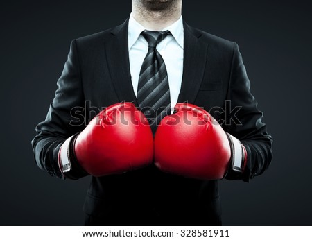 businessman in boxing gloves isolated on gray - stock photo