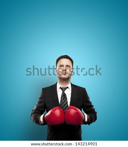 businessman in boxing gloves on a blue background - stock photo