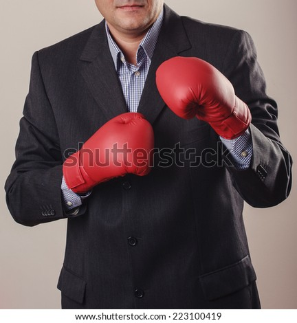 Businessman in boxing gloves on background