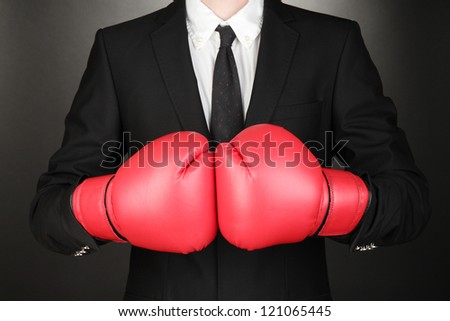 Businessman in boxing gloves on grey background - stock photo