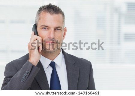 Businessman in bright office looking at camera while having a phone call  - stock photo