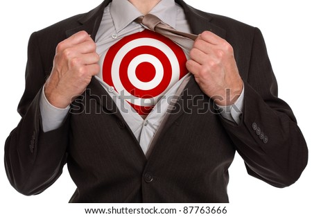 Businessman in classic superman pose tearing his shirt open to reveal target symbol on chest - stock photo
