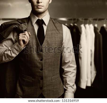 Businessman in classic vest against row of suits - stock photo