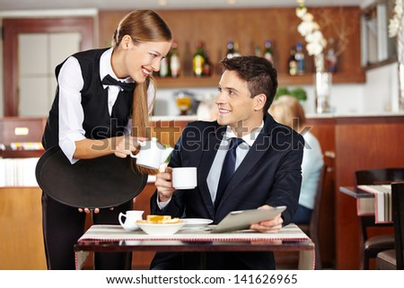 Businessman in coffee shop flirting with female waiter - stock photo