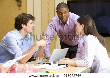 Businessman in conversation with colleagues at table with laptop computer - stock photo