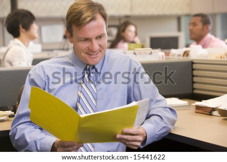 Businessman in cubicle with folder smiling - stock photo
