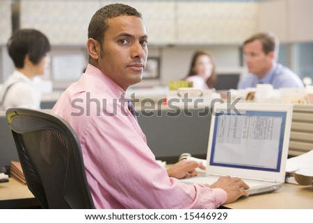 Businessman in cubicle with laptop - stock photo