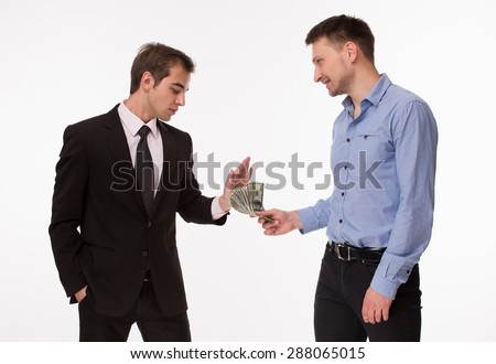 Businessman in dark-coloured business suit rejecting money from man in blue-coloured shirt. Two men posing on white. - stock photo