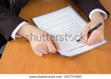 Businessman in dark suit and blue shirt sitting at office desk signing a contract with shallow focus on signature. - stock photo