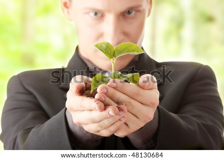 Businessman in dark suit holding small plant in his hands - growth concept