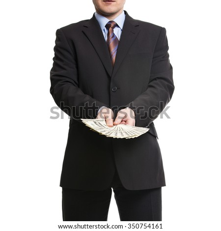 Businessman in dark suit with a bunch of American Dollars. Isolated on white background.