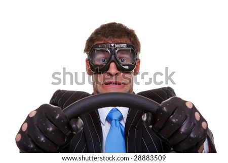 Businessman in driving gloves and goggles with a look of panic on his face, isolated on white background. - stock photo