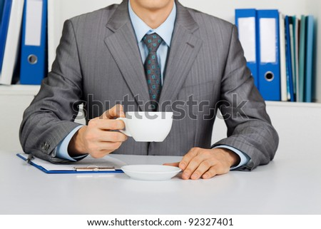 Businessman in elegant suit hold cup of coffee or tea, unrecognizable person sitting at the desk at office, concept of break - stock photo