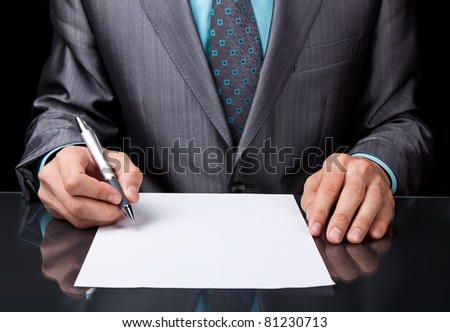 Businessman in elegant suit working with documents sign up contract, business plan sitting at desk working, concept of hold blank, empty sheet of white paper over black background.
