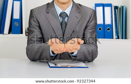 Businessman in elegant suits asking for money, man in blue suit lending a helping hand, sitting at the desk at office - stock photo