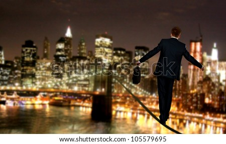 Businessman in equilibrium on a rope - stock photo
