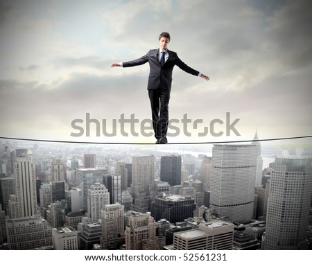 Businessman in equilibrium on a rope over a cityscape - stock photo