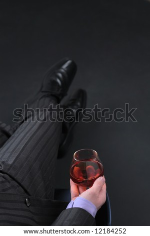 Businessman in formal dress relax with glass of cognac over black background. Image with copyspace. Focus on glass. - stock photo