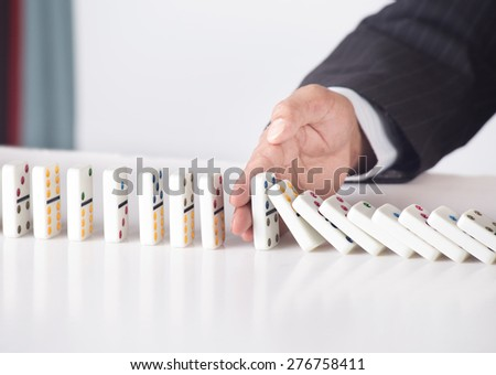 Businessman in formal suit stopping falling dominoes - concept for strategy and problem solving - stock photo