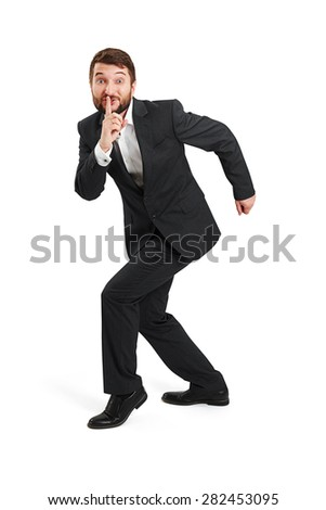 businessman in formal wear showing silent sign and walking on tiptoe. isolated on white background - stock photo