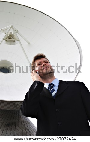 Businessman in front of big satellite dish isolated on white